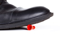Big black boot crushing a small red game piece. Little object pinned down about to be destroyed under a large shoe, closeup Big vs small rich vs poor business social abstract concept, white background