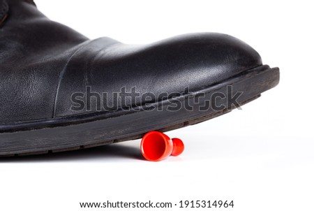Big black boot crushing a small red game piece. Little object pinned down about to be destroyed under a large shoe, closeup Big vs small rich vs poor business social abstract concept, white background Foto stock ©
