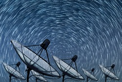 Big black satellite dish on Beautiful spiral star trail at night background, transmission data. digital technology sky background.