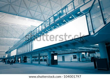 big Blank Billboard in airport with moving blurred passenger, blue tune, shot in asia