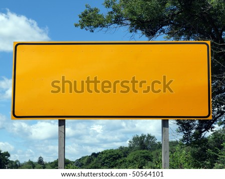 Big blank highway sign with blue sky and summer greens.
