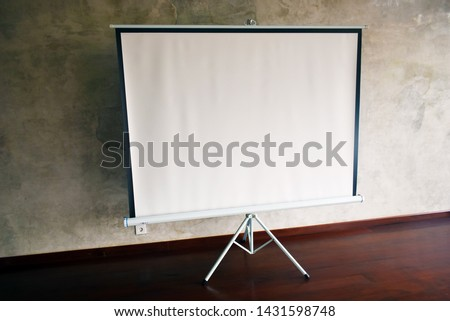 Big Blank Portable Tripod Projection Screen in Yoga Hall Beautiful Background Wall. Side Angle