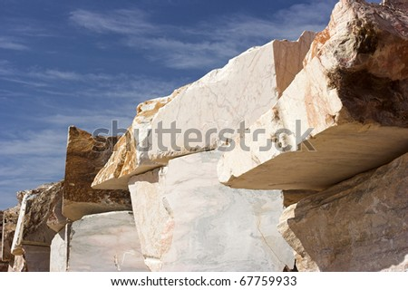 Big blocks of raw marble in a quarry in Estremoz (Alentejo - Portugal) against deep blue sky