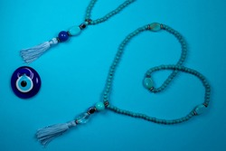 Big Blue oriental Japa Mala (mala Sanskrit) in a shape of heart and greek eye - Blue background