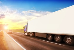 Big blue truck driving fast with a white trailer with blank space for text on a countryside road with other cars against a blue sky with a sunset