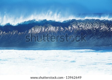 Big blue wave breaking and trowing off spray.  Horizontally framed shot.