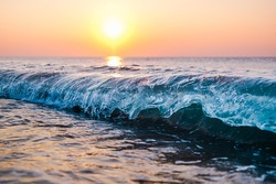Big Blue Wave Breaking in Ocean View at Sunrise with Colorful Pastel Sky in Tropical Island Nature Scene and Sun Reflection in Sea Water