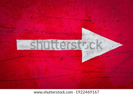Big bold white arrow on a bright red background, vignetted. Stockfoto ©