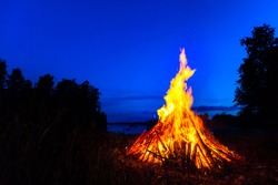 Big bonfire against blue night sky