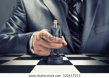 Big boss playing chess using businessman