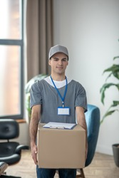 Big box. Delivery courrier in a cap standing with a big box in his hands