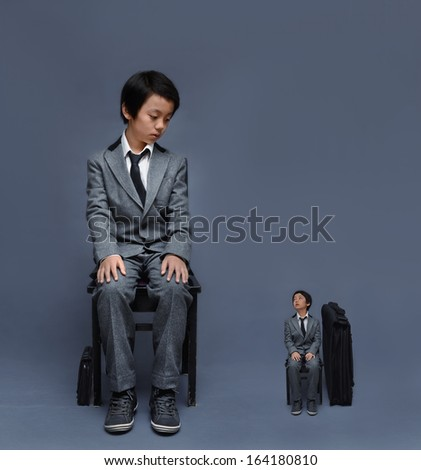 Big boy & small case, small boy & big case in business suit (uniform) sitting on chair (future career concept)