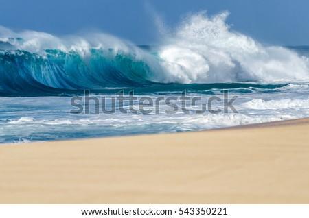 Big breaking Ocean wave on a sandy beach on the north shore of Oahu Hawaii #543350221
