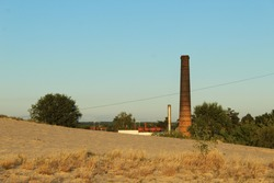 big brick boiler house chimney against the background of sand and blue blue sky with between green bushes