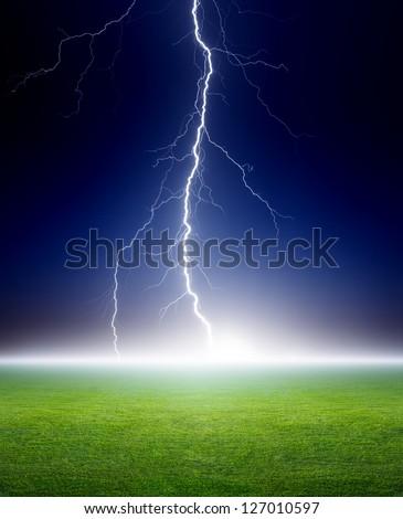Big bright lightning, green grass field, dark blue night sky