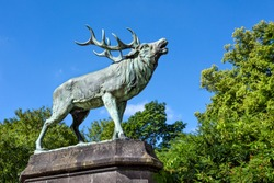 Big bronze statue of an antlered belling stag in a green park with trees and blue sky in the background - concept deer animal mammal wildlife nature environment sculpture strength kitsch from below
