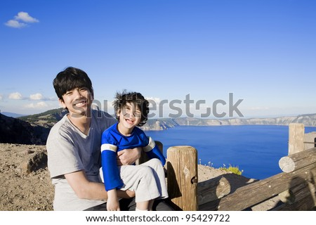 Big brother holding smiling disabled little boy with Oregon's famous Crater Lake in the background. Child has cerebral palsy