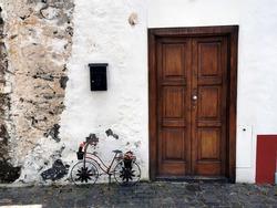 Big brown door with a decorative small bike in the city of Santa Cruz, La Palma, Spain