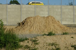 big brown pile of sand outside in green grass near the gray concrete wall of the fence