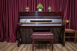 Big brown wooden piano and red bench close up in room . Old wooden piano keys on wooden musical instrument in front view . modern red piano bench