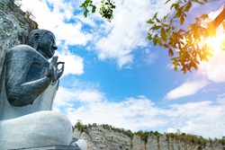 Big Buddha carved on cliff of limestone or rock mountain to Buddha sculpture for worship with sunlight and blue sky background,Wat Khao Tamtiem Temple, U Thong District, Suphanburi Province Thailand