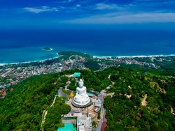 Big Buddha Phuket thailand views of Kata Beach karon beach and challong Bay. Green lush mountains blue skies and turquoise beaches. Big Buddha statue made of small marble blocks is very beautiful
