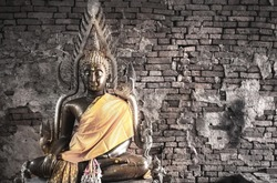 Big buddha statue at Brick wall background. Metal sculpture, Buddha statue to worship.