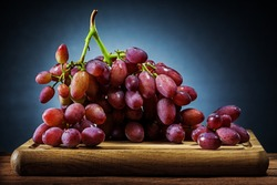 big  bunch of rose grape on wooden cutting board and black gradient background