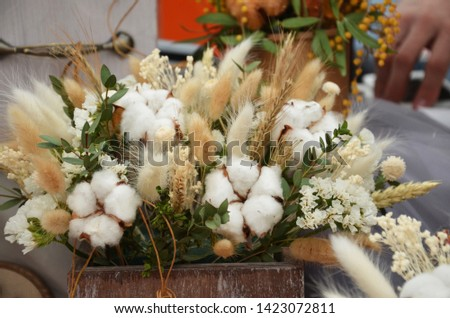 Big bunches of cotton standing in vases and hand made wooden wreaths by the window at the florist shop, #1423072811
