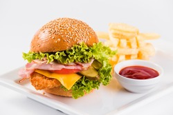 Big burger french fries and sauce on a white background close up