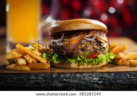 Big burger with fries on the wooden table