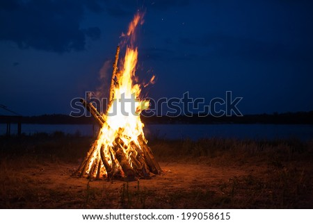 Big campfire at the river after sunset