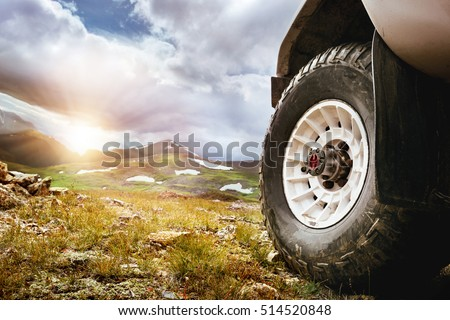 Big car wheel on mountains and sunset backdrop. Offroad 4x4 concept