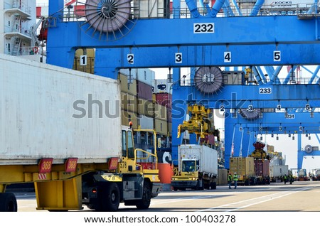 Big cargo container ship freighter vessel in a container seaport during transportation of cargo in containers by cranes and lorry truck.