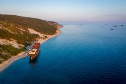 Big cargo ship running aground. view from above. Panorama of the sea bay at sunset