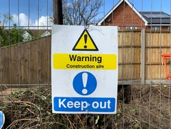Big caution sign on metal fence. Warning construction site, keep out. The sign is clearly print with warning symbol on yellow background. Building site, legal requirement, health and safety concept.