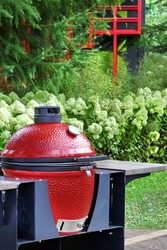 Big Ceramic Red Egg BBQ Grill. Barbecue Charcoal Grill For Cookout Food. Ceramic Barbeque Grill And Smoker On The Backyard Lawn Or Restaurant Outdoor Terrace.