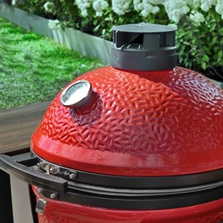 Big Ceramic Red Egg BBQ Grill. Kamado Barbecue Charcoal Grill For Cookout Food. Ceramic Barbeque Grill And Smoker On The Backyard Lawn Or Restaurant Outdoor Terrace.