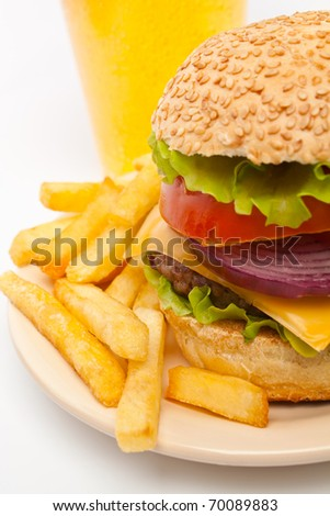big cheeseburger garnished with french fries on a  plate and a glass of lemonade on white background