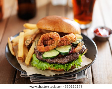 big cheeseburger loaded with onion rings, bacon and bbq suace served with fries #330112178