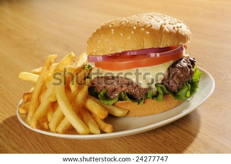 Big cheeseburger on white plate with french fries.