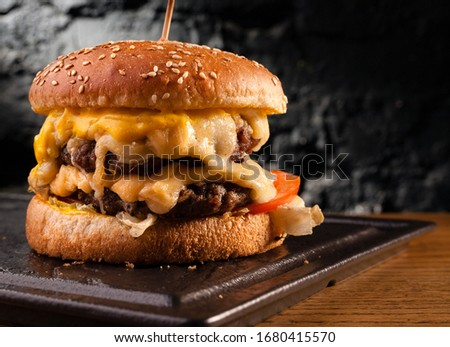 Big cheeseburger with lots of cheese. Stock photo side view of a cheeseburger on a black brick wall background. Сток-фото ©