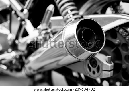 Big chromed exhaust on motorcycle, photographed from behind. Black and white photo. #289634702