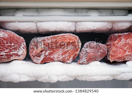Big chunks of red beef lying on the freezer shelves with a big quantity of frozen ice and snow. This freezer hasn't been thawed in a long time.