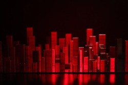 Big city sky scrapers reflecting in the water, imitation made of batch staples composition in red light on reflecting surface and black background