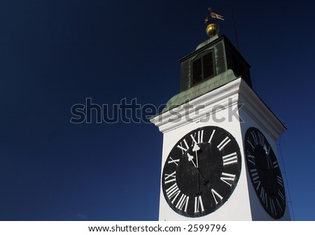 Big clock tower on the Petrovaradin's fort on the right bank of Danube river - stock photo