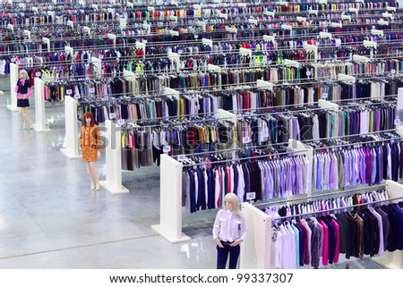 Big clothing store, dummies and many rows with hangers, variety of sizes