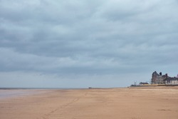 Big cloudy sky above empty, deserted sandy beach with vintage looking old buildings in distance, in seaside town and resort of Redcar on moody, rainy day on the East coast of Northern England.