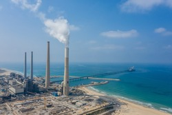 Big coal power station with tall chimnies and coal conductor and white steam - aerial shot in Hadera