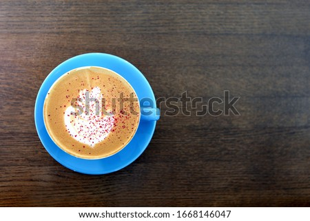Big Coffee cup with milk on the wooden table. cappuccino or latte drink, cup of coffee on brown table flat lay view. Cup of cafe au lait. Milk paintings or latte art. Hot Coffee in a blue mug